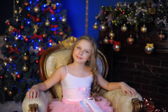Cute girl sitting in a chair at the Christmas tree Royalty Free Stock Image