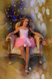 Cute girl sitting in a chair at the Christmas tree Royalty Free Stock Photography