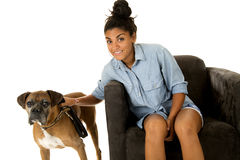 Cute girl sitting in a chair with her dog a boxer next to her Royalty Free Stock Photo