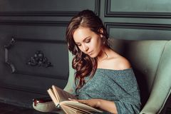 Cute girl sitting in a chair and reading a book in the office stock images