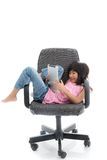 Cute girl  sitting on a chair using Digital Tablet Stock Images