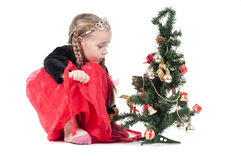 Cute girl sitting with christmas tree Stock Photography