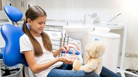 Cute girl sitting in dentist chair and showing her teddy bear how to properly clean teeth. Girl sitting in dentist chair and showing her teddy bear how to stock photos