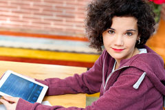 Cute girl sitting at desk with tablet. Stock Photos