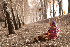 Cute girl sitting on fallen autumn leaves while leafs falling and playing with dolls Royalty Free Stock Image