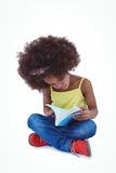 Cute girl sitting on the floor holding book Stock Photography