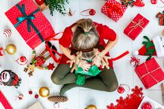 Cute Girl Sitting on the Floor Opening Christmas Present. Cute Girl Sitting on the Floor Opening Christmas Present, Top View stock image