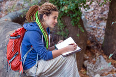 Cute Girl sitting in Forest and drawing sketch in her note book Royalty Free Stock Images