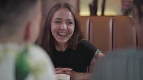 Cute girl sitting in front of two male friends drinking coffee. Young woman and two guys communicate sitting at a table stock video footage