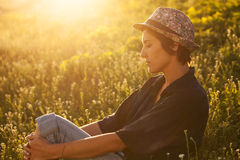 Cute girl sitting in the grass on a sunny evening Stock Images