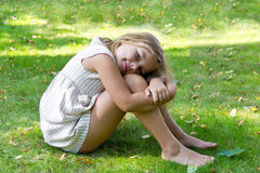 Cute girl sitting on green grass Royalty Free Stock Images
