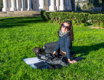 Cute girl sitting on green grass smiling with tablet and notebooks Stock Images