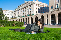 Cute girl sitting on green grass talking on the phone and writing something with tablet and notebooks.  royalty free stock images