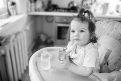 Cute girl sitting in the highchair Stock Images