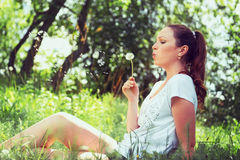 Cute girl sitting in a park and blowing on the dandelion. Natura Stock Image