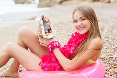 Cute girl is sitting on pink rubber ring with Royalty Free Stock Photography