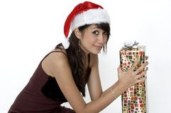 Cute Girl Sitting With a Present. Sitting Down With A Present In A Santa Hat royalty free stock images