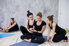 Cute girl sitting and socializing with the group after their yoga class royalty free stock photo