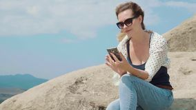 Cute girl sitting on a stone, against the sky and the mountains prints a message and speaks on the phone. Casual wear stock video footage