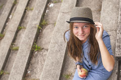 Cute girl sitting on the stone steps, top view, looking at the camera. Cute young girl sitting on the stone steps, top view, looking at the camera Stock Photography