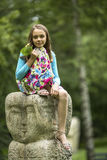 Cute  girl sitting on a stone totem in the Park. Stock Photo