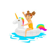 Cute girl sitting on swimming floating inflatable ring in shape of unicorn Stock Image