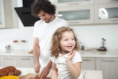 Cute girl sitting on table near her father in cook room stock photography