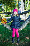 Cute girl sitting on tree branch in autumn park Stock Photo