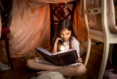 Cute girl sitting under blanket and reading a book Stock Image