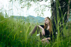 Cute girl sitting under tree Royalty Free Stock Images