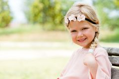 Cute girl sitting on wooden bench in park. Royalty Free Stock Photo