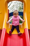 Cute girl sitting at yellow slide Stock Photography