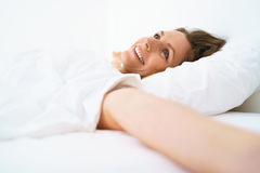 Cute girl sleeping in bed waking up stretching and smiling Stock Image