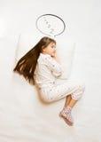 Cute girl sleeping on big cushion with speech bubble Stock Photography