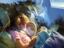 Cute girl sleeping in car. A little girl inside a car, sleeping. Car window reflexion Royalty Free Stock Images