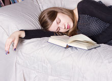 Cute girl sleeping while holding a book lying Stock Photography