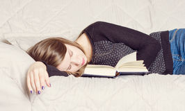 Cute girl sleeping while holding a book lying Royalty Free Stock Photo