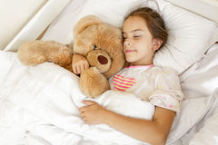 Cute girl sleeping and hugging big teddy bear at bed Royalty Free Stock Image