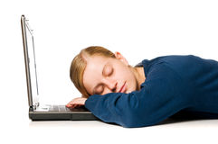 Cute girl sleeping on laptop. Detail of a cute blondie girl sleeping on her laptop computer, isolated on white background royalty free stock photo