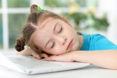 Cute girl sleeping near laptop Stock Image