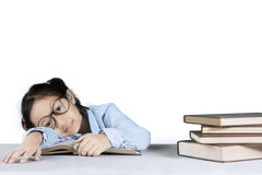 Cute girl sleeping with a pile of books. Image of cute girl looks tired while reading a book and sleeping with a pile of books on the table Stock Photo
