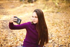 Cute girl with a smartphone in the autumn forest. royalty free stock images