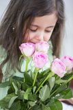 Cute girl smelling roses at home Royalty Free Stock Photo