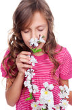 Cute girl smelling spring flowers Royalty Free Stock Photos