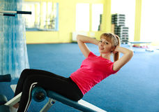 Cute girl with a smile, doing press exercise on the bench. In the gym Stock Image