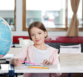 Cute Girl Smiling With Books And Globe At Desk Stock Image