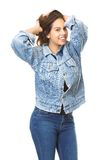 Cute girl smiling with hands in hair wearing jeans Stock Images