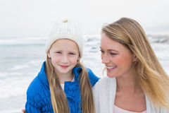 Cute girl with smiling mother relaxing at beach Stock Photography