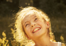 Cute girl smiling in the sun.Toned Stock Image