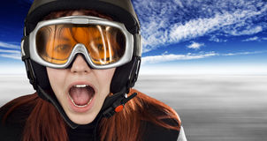 Cute girl with snowboarding helmet and goggles. Cute girl with red hair wearing a ski helmet and orange goggles acting surprised and yelling. Feeling cold royalty free stock photography